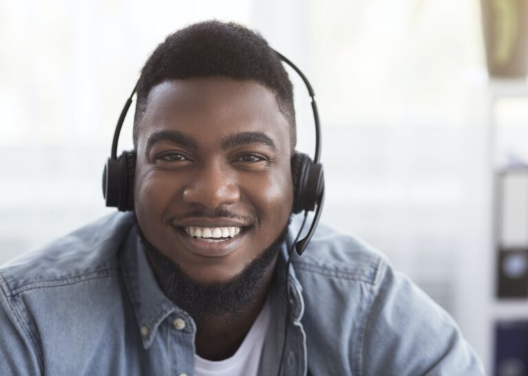 Portrait of friendly black customer support manager in headset